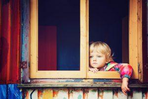 enfant regardant tristement l'extérieur par la fenêtre
